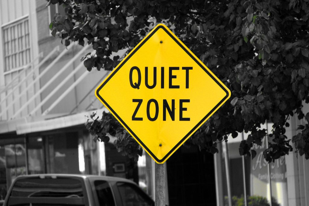 Black and white background with yellow road sign reading 'Quiet Zone' for Autism Hour